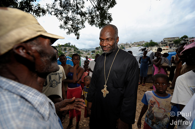 Father Barnabas, a priest of the Greek Orthodox parish of St. Jean de Freres in the Bobin neighborhood of Port-au-Prince, Haiti, visits with people left homeless by the January 2010 earthquake who are living in a tent city in the neighborhood. .