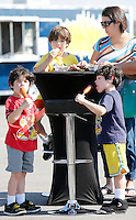 NWA Democrat-Gazette/DAVID GOTTSCHALK  Brayden Myers, 5, (from left) eats lunch with his family Alexander, 7, Austin, 5, and their mother Angelina Tuesday, September 29, 2015 in the parking lot of the Walmart AMP during the second annual Food Truck Feastival. Proceeds from the lunch time event benefitted the United Way of Northwest Arkansas.