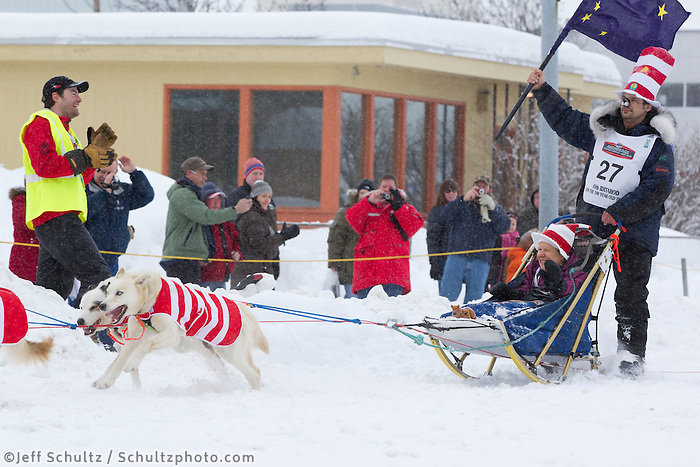 Saturday, March 3, 2012 Hugh Neff waves an Alaska State flag while wearing his cat-in-the-hat, hat on 4th avenue during the Ceremonial Start of Iditarod 2012 in Anchorage, Alaska.