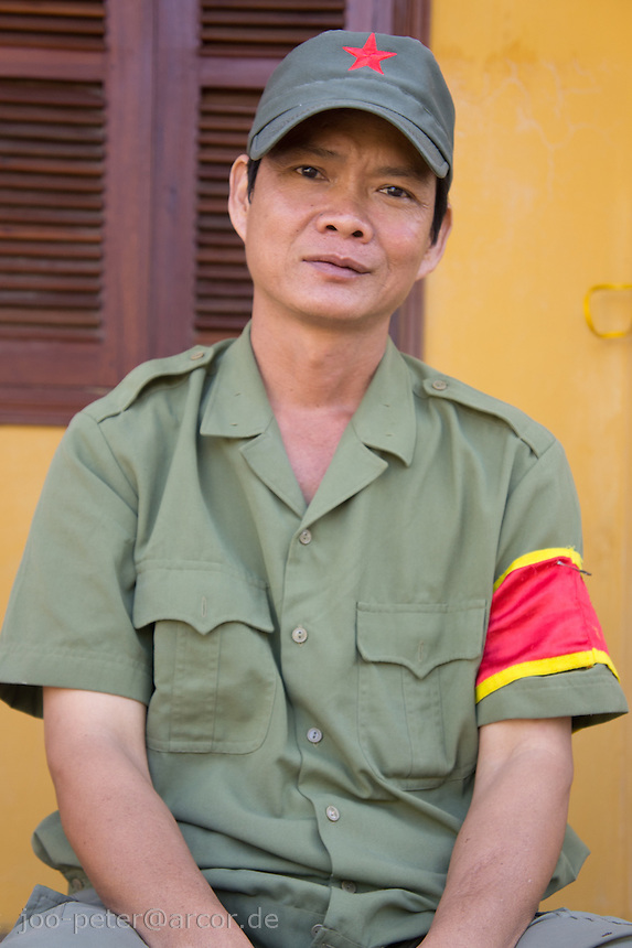 neighborhood marshal  enjoys his peaceful guarding time in the streets of Hoi An, Vietnam