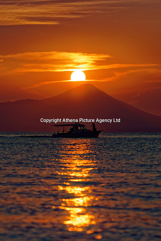 A fishing boat sails as the sun sets -marking the longest day of the year during the summer solstice- over the seaside port town of Oropos, 30 miles (50 km) north of Athens, Greece. Friday 21 June 2019