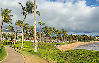 A woman and man walk the scenic coastal pathway in Wailea between a resort with condominiums and Wailea Beach, South Maui.
