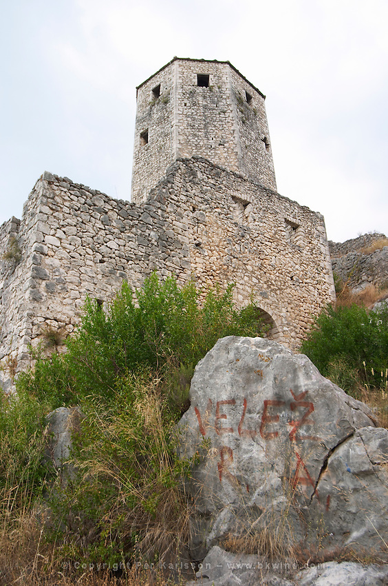 View of the tower fortress, graffiti on a stone 'Velez R A'. Pocitelj historic Muslim and Christian village near Mostar. Federation Bosne i Hercegovine. Bosnia Herzegovina, Europe.