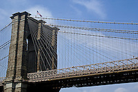 The towering, center arches of Brooklyn Bridge, photographed from below the bridge, wiith the Ameriican Flag flying in the wind against the clouded, blue sky.
