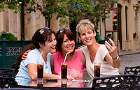 Tourist girl friends relax with drinks and take Iphone photos and have fun in Europe anywhere to just be friends