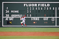 The operator of the manual scoreboard for the Greenville Drive has a good vantage point to watch left fielder Felix Sanchez (3) field a single hit off the wall by Jose Peraza  of the Rome Braves in the third inning of a game on Wednesday, August 21, 2013, at Fluor Field at the West End in Greenville, South Carolina. Rome picked up the win, 6-2. (Tom Priddy/Four Seam Images)
