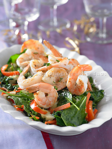 Spinach and red pepper salad topped with large shrimp. Festive table setting with purple tablecloth, ribbon, wine glasses