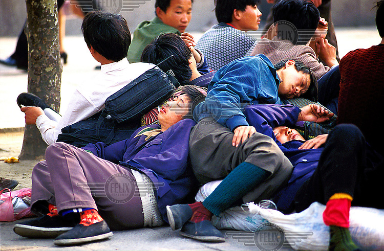 Mark Henley/Panos Pictures..China, Shanghai..Migrant labourers in search of work, outside the main railway station, sleeping together on their belongings in rice sacks.