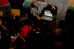 Andean Mountain Cat (Leopardus jacobita) biologist, Juan Reppucci, showing camera trap images from the local area to school children, Loma Blanca, Abra Granada, Andes, northwestern Argentina