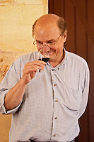 Jean-Francois Quenin, owner and wine maker, in the tasting room tasting a glass of his wine  Chateau de Pressac St Etienne de Lisse  Saint Emilion  Bordeaux Gironde Aquitaine France