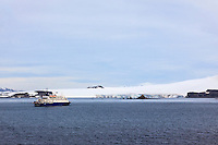"The ""Sea Spirit"" waits offshore as her guests explore the nearby Aitcho Island in the South Shetland Islands near the Antarctic Peninsula."