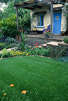 Rustic front porch & pretty blue door and cute cottage looks out on perennial and annual flowers border and lovely lush gorgeous lawn grass, flowers