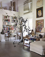 The large living room is the perfect showcase for an extensive and varied collection of paintings and sculptures including this near life-size tree surrounded by fallen metal leaves