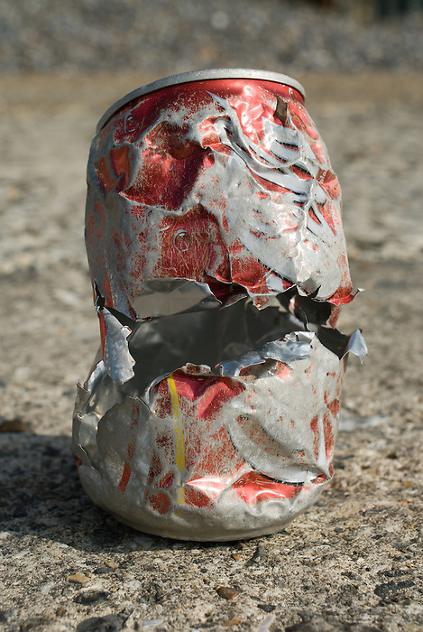 A beat up soft drink can, torn and jagged, found on a beach.