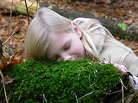 Kinder im Wald, Kinder erleben die Natur im Wald, Walderlebnistag, Schulkinder bei einer Waldexkursion, Exkursion, Mädchen spürt, wie weich Moos ist. Waldtag, Waldpädagogik, Naturpädagogik