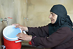 A woman fills a container with safe drinking water in the El Rahmeh settlement of Syrian refugees in Bhannine, a village in the Akkar district of northern Lebanon. Lebanon hosts some 1.5 million refugees from Syria, yet allows no large camps to be established. So refugees have moved into poor neighborhoods or established small informal settlements in border areas. International Orthodox Christian Charities, a member of the ACT Alliance, provides a variety of support for families in this settlement, including water and sanitation facilities.