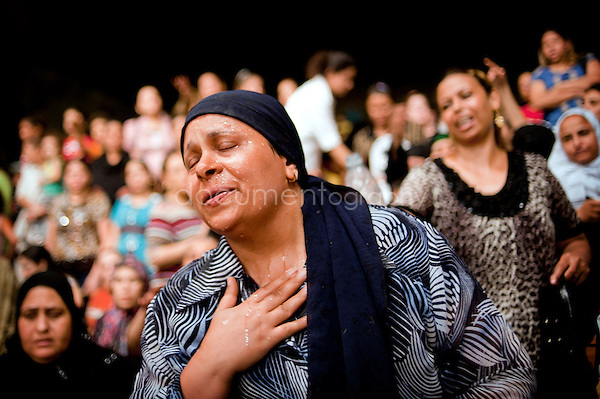 A Muslim woman in the St. Simeon Church has just received holy water on her face by Father Samaan.<br />