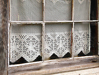 A lace curtain adournes an old window in a building at the Billie Creek Village restoration in Rockville, Indiana