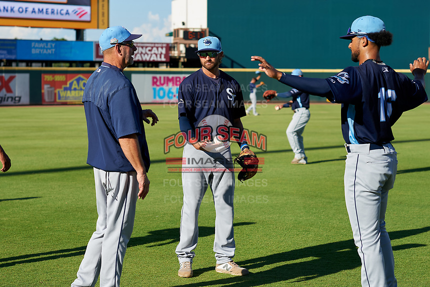Charlotte Stone Crabs coach Joe Szekely (left) talks with Zach Rutherford (center) and Garrett Whitley (16) during warmups before a Florida State League game against the Bradenton Marauders on July 30, 2019 at LECOM Park in Bradenton, Florida.  Charlotte defeated Bradenton 5-0.  (Mike Janes/Four Seam Images)