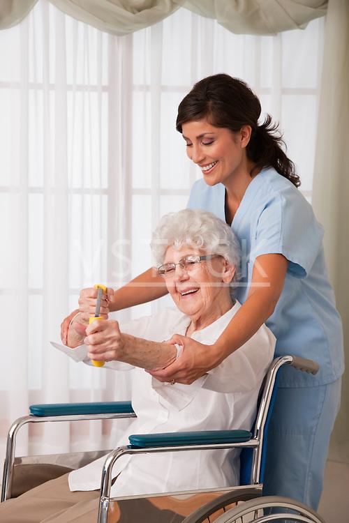 USA, Illinois, Metamora, Female nurse assisting senior woman on wheelchair using exercise band