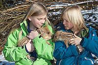 Wildschwein, Kinder mit verwaistem Jungtier im winterlichen Garten, wird in menschlicher Obhut großgezogen, Jungtier wird von Hand aufgezogen, Aufzucht eines Wildtieres, Wild-Schwein, Schwarzwild, Schwarz-Wild, Frischling, Junges, Jungtier, Tierkind, Tierbaby, Tierbabies, Schwein, Sus scrofa, wild boar, pig
