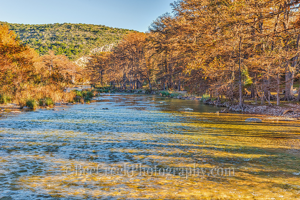 This is the Frio River as it flows through Con Can Texas as the sun is low in the sky casting these shadows of light and dark across the waters.
