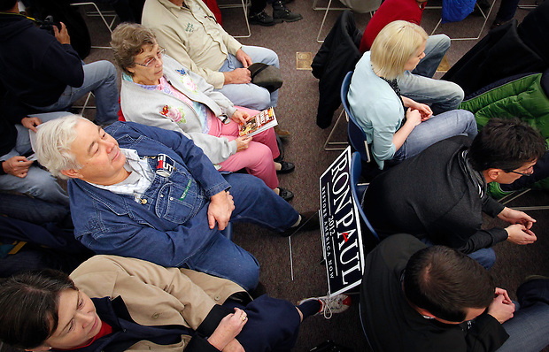 Ron Paul supporter Robert McNamara, left center, of Spillville, Iowa sits with a newly-claimed campaign sign while waiting for Congressman Paul to arrive to a campaign stop in Waverly on December 9.