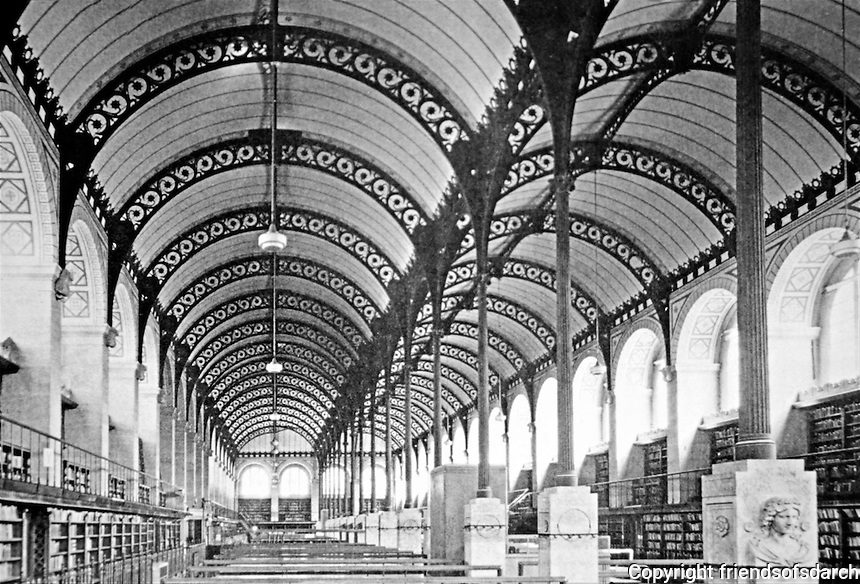 Bibliotheque Sainte-Genevieve, Paris. Henri Labrouste, Architect. 2nd floor Reading Room with slender, cast-iron Ionic columns dividing the space into twin aisles and supporting openwork iron arches that carry barrel vaults of plaster reinforced by iron mesh.Historic photo.