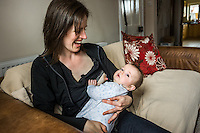 A young woman breastfeeds her baby at home while sitting on  sofa in her living room. The baby breaks off from her nipple to look at the camera.<br /> <br /> 15/05/2012<br /> Hampshire, England, UK