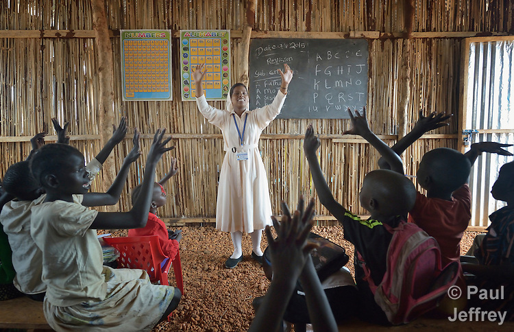 Sister Mariya Soosai, a member of the Daughters of Mary Immaculate, leads a group of children in an arithmetic class in a camp for internally displaced families inside a United Nations base in Juba, South Sudan. Some 34,000 people have sought protection here since violence broke out in December 2013. More than 112,000 people currently live on UN bases in the war-torn country, most of them afraid of tribally targeted violence. Ten DMI sisters from India work in the Juba camp, providing counseling and psycho-social support for women and children, teaching children in makeshift schools, and providing food to hungry families.