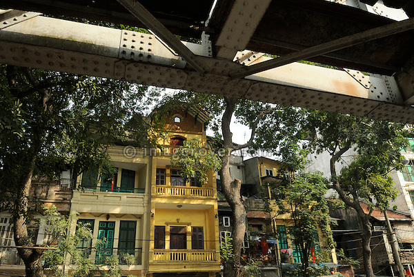 Asia, Vietnam, Hanoi. Hanoi old quarter. French colonial style housing next to the railway bridge.
