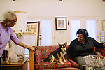 Maxine McNair (left) readies to sit on the couch next to her daughter Kimberly Brock in her Birmingham, Alabama home August 13, 2013. Maxine's daughter Denise was one of four girls killed in a bomb blast at 16th Street Baptist Church in Birmingham, Alabama in 1963.