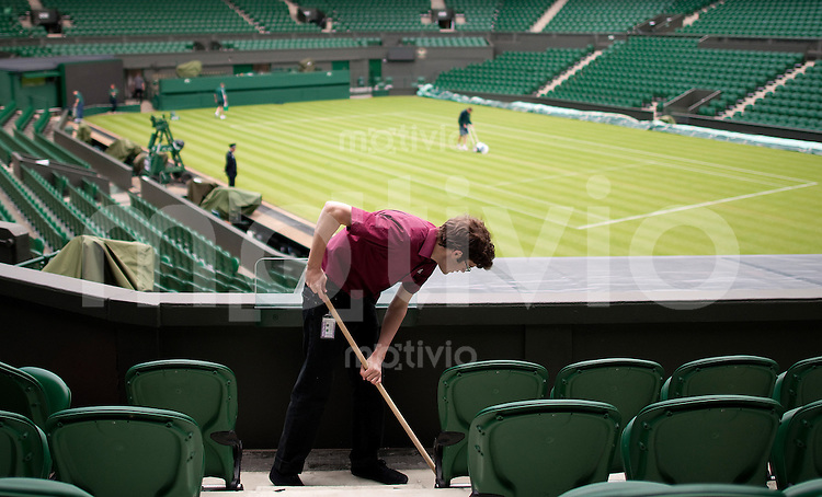 A worker cleans the seating area on Centre Court Preparation for The Wimbledon Championships 2010 The All England Lawn Tennis & Croquet Club  Saturday Pre Championships Saturday 18/06/2010
