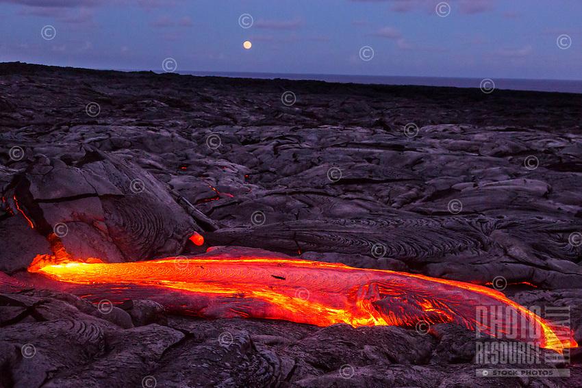 Molten lava glowing and full moon rising at dusk in Hawai'i Volcanoes National Park, Hawai'i Island.