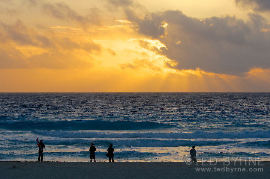 Small group of people watching a golden sunrise on a beach