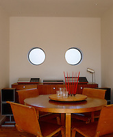 This retro style dining room has a pair of porthole windows and a vintage stereo on a side board