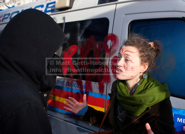 A female protester talks to a masked demonstrator in an effort to stop him and others from attacking an empty police van left of Whitehall during the second student protest. 24/11/10