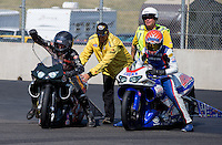 Jul. 21, 2013; Morrison, CO, USA: NHRA safety safari members help pro stock motorcycle riders Shawn Gann (left) and Hector Arana Jr at the end of the track during the Mile High Nationals at Bandimere Speedway. Mandatory Credit: Mark J. Rebilas-
