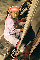 In small factories throughout China's Xinjiang Uyghur Autonomous Region, young Uyghur women work creating silk and wool carpets..