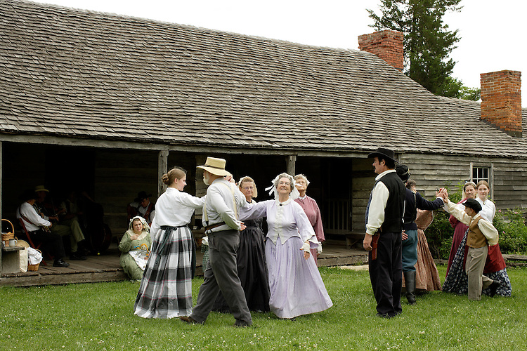 Volunteers in period clothing dance in front of the 1850 Tavern while the band plays on the porch at Missouri Town 1855. This old Missouri town is located on the east side of Lake Jacomo in Fleming Park in Blue Springs, MO. Missouri Town 1855 is a collection of original mid-19th century structures that were relocated from several Missouri counties to represent a typical 1850's farming community.