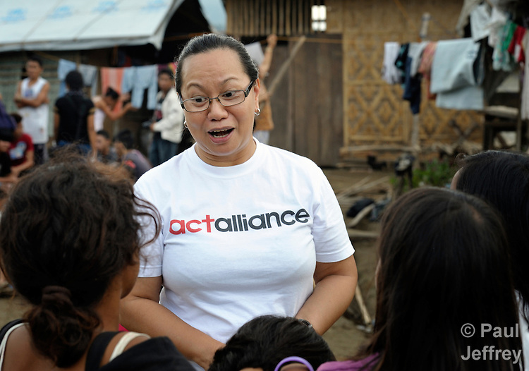 After the passage of Typhoon Bopha, Minnie Anne Calub, the emergency coordinator for the National Council of Churches of the Philippines, talks with children displaced by the storm in Iligan, on the southern Philippines island of Mindanao. The NCCP is a member of the ACT Alliance, which sponsored a food distribution in this community..