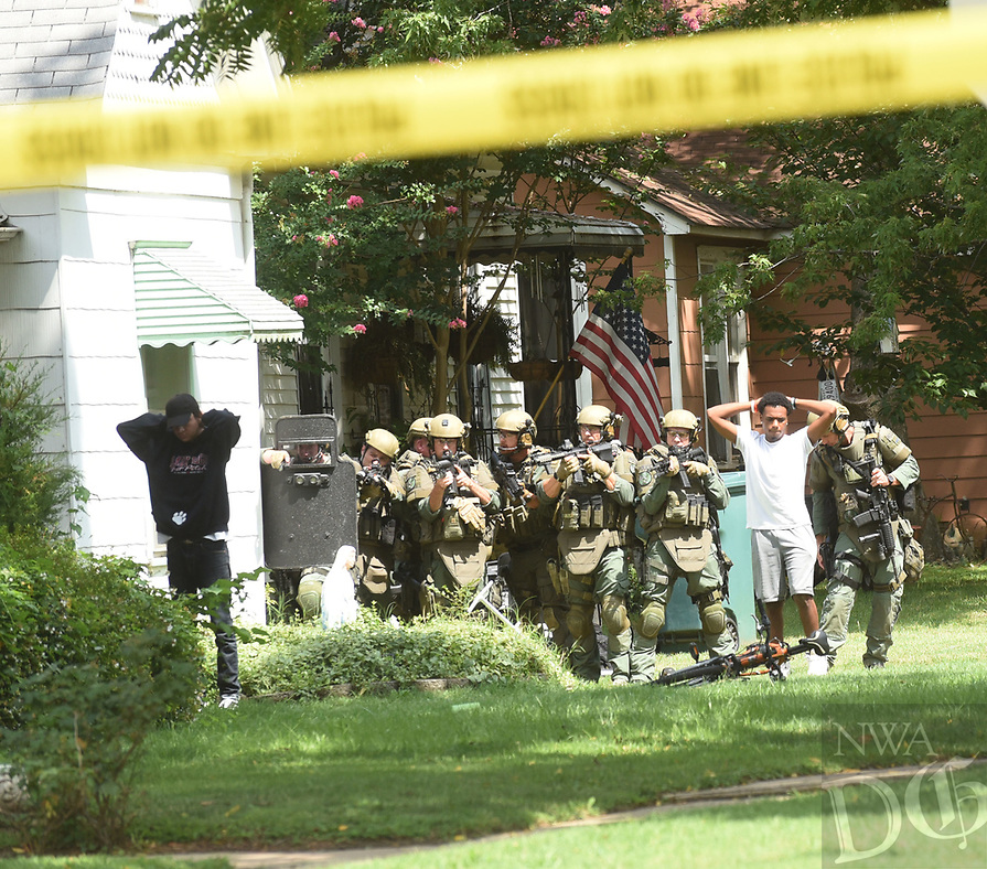 NWA Democrat-Gazette/FLIP PUTTHOFF <br />People who refused to emerge Wednesday Aug. 8 2018 from a home near Third and Persimmon streets in Rogers are searched by police after they surrendered. A standoff lasted about three hours when Rogers police attempted to serve a warrant on a suspect who then barricated himself in the home.