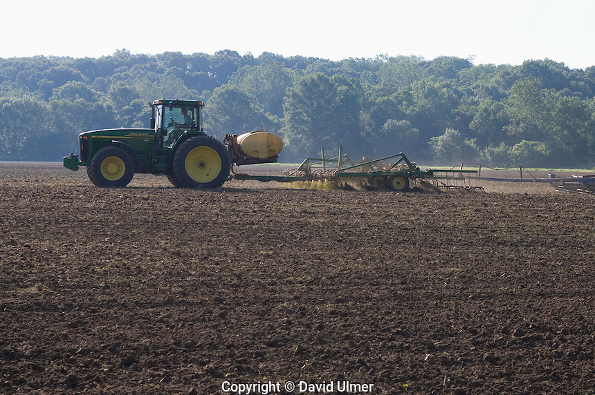 Tractors pull discs and spray rigs put down pre-emergent over the field