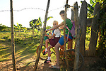 Brother and sister bike through the gate to their farm<br /> Outside Trinidad, Cuba