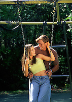 A smiling young couple plays on a swing.