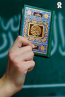 Boy's hand (12-13) holding Koran, Saudi Arabia flag in background (Licence this image exclusively with Getty: http://www.gettyimages.com/detail/sb10066226f-001 )