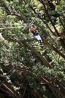 Woman Zip-lining through the air and rainforest with Kohala Ziplining in North Kohala on the Big Island.