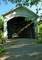 View looking east at the entrance of Narrows Covered Bridge, built in 1883 by Joseph A. Britton, over Sugar Creek in Parke County, Indiana, USA. The entrances to covered bridges built during this time period often resembled barns, so that horses would more willingly enter.
