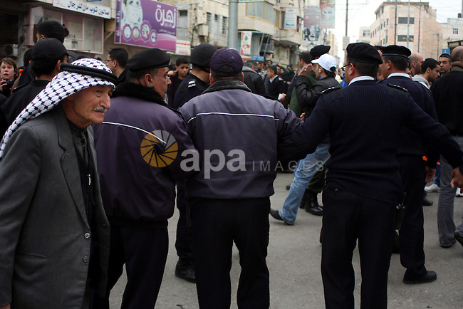 Palestinian riot-police take positions to prevent clashes between Palestinian protesters and Israeli security forces, not pictured, during a demonstration against the closure of Shuhada street to Palestinians, in the West Bank city of Hebron 25 February 2011. The activists gathered on Friday calling for the end to the closure of Shuhada street, which was closed by the Israeli army in 1994 following the Hebron mosque massacre by Baruch Goldstein, an Israeli settler, who went on a rampage inside Al Ibrahimi Mosque, killing 29 Palestinian worshippers.. Photo by Najeh Hashlamoun