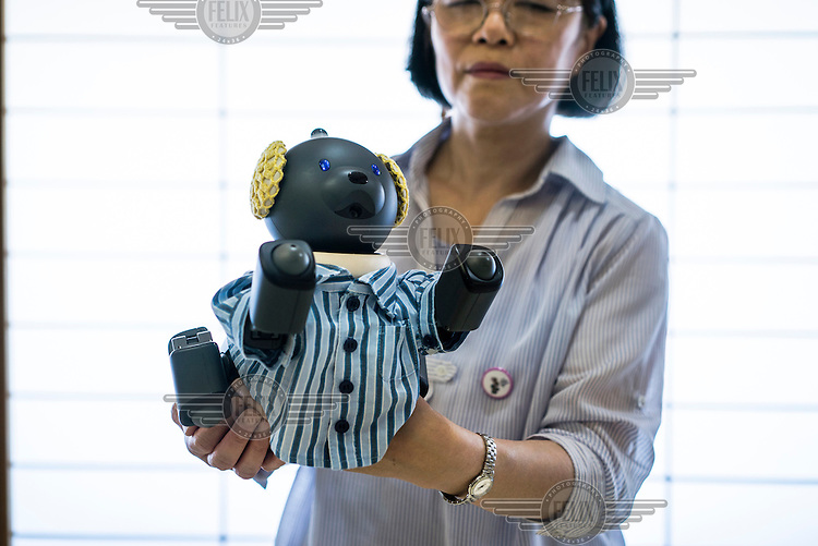 Fumiyo Kawara, 65, poses with her AIBO at an AIBO meeting outside of Tokyo. In 1999, Sony released a series of robotic pets called AIBO or Artificial Intelligence Robot. In 2006, they discontinued the AIBO line and then in 2014, discontinued all reparair services on the AIBO. A small community of AIBO owners still exists and a new repair service has emerged to help keep the AIBOs running.